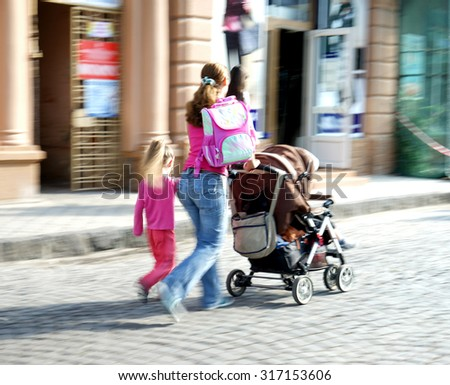 Mother with small child and a stroller walking down the street. Intentional motion blur - stock photo