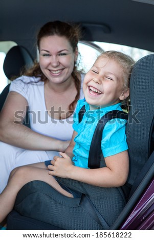 Mother with small daughter laughing on the back seat of car - stock photo
