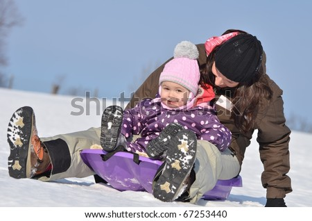 Mother with small girl going down in bobsleigh