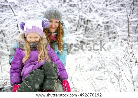 mother with smiling daughter on a winter walk