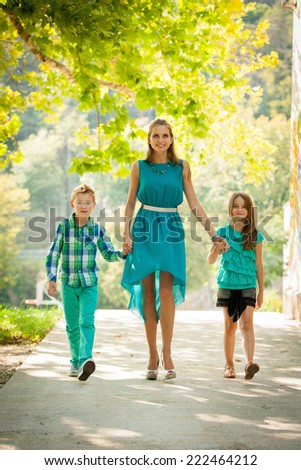 Mother with son adn daughter on a walk in park in late summer afternoon - stock photo
