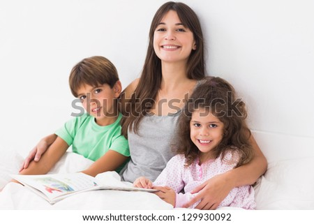 Mother with son and daughter reading book together in bed