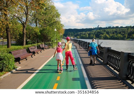 Mother with son and daughter ride on roller skates on luzhnetskaya quay river Moscow