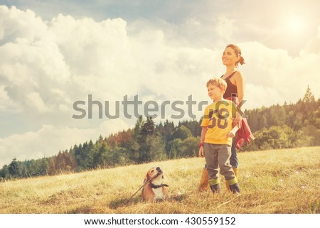 Mother with son and his dog walk on the golden field - stock photo
