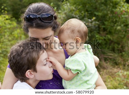 mother with son and infant daughter in loving embrace - stock photo