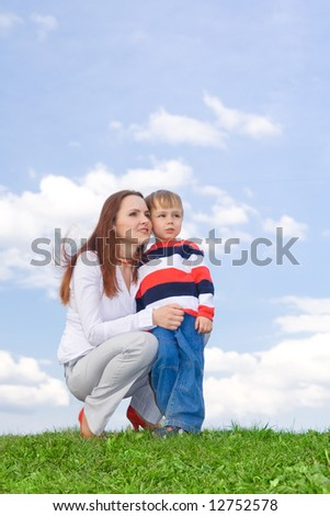Mother with son at green grass looking up to blue sky - stock photo