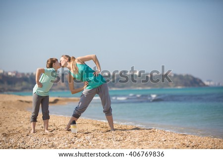 Mother with son exercising on the beach at morning