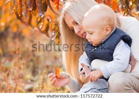 Mother with son in autumn peach garden - stock photo