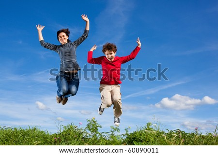 Mother with son jumping, running outdoor against blue sky