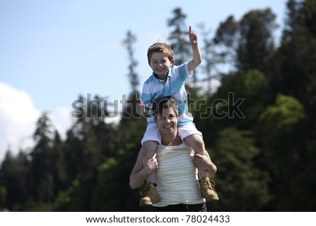 mother with son on her shoulders at a beach