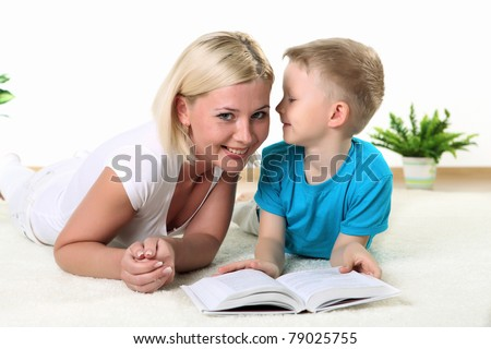 mother with son reading a book on the floor in studio