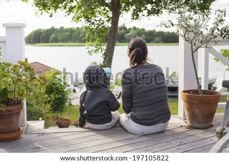 Mother with son sitting on porch and looking at water - stock photo