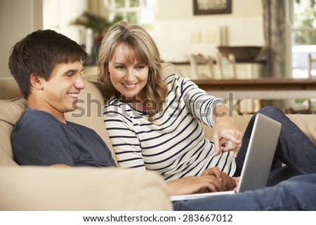 Mother With Teenage Son Sitting On Sofa At Home Using Laptop - stock photo