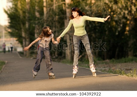 Mother with the daughter go on  roller skates, outdoor, in the evening summer - stock photo