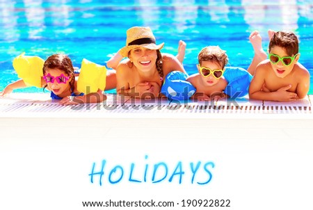 Mother with three children having fun in the pool, swimming in blue transparent water, active cheerful family spending summer holidays together