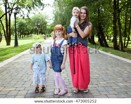 Mother with  three children standing on the road in the park