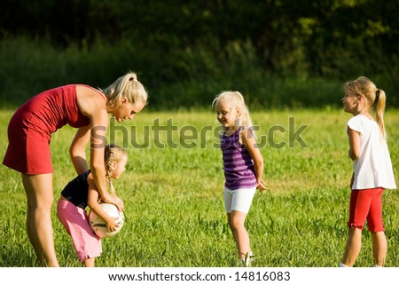 Mother with three daughters playing football (well, soccer for North America) on a green, sunlit meadow - stock photo