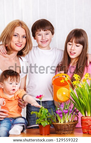 Mother with three kids watering flowers - stock photo