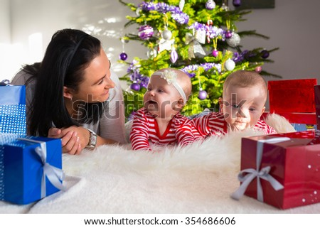 Mother with twins unpacking presents under the Christmas tree - stock photo