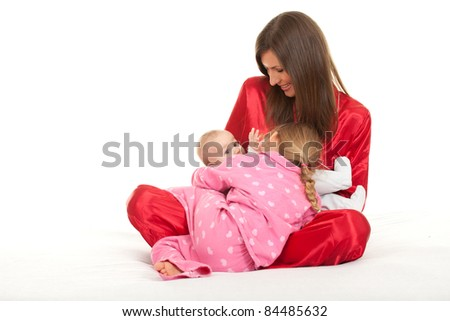 mother with two children in white bedding - stock photo