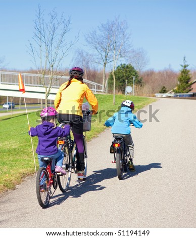 Mother with two children on bikes - stock photo