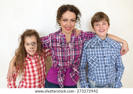 mother with two children posing on white background closeup - stock photo