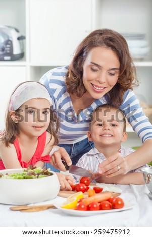 Mother with two children preparing meal in the kitchen - stock photo