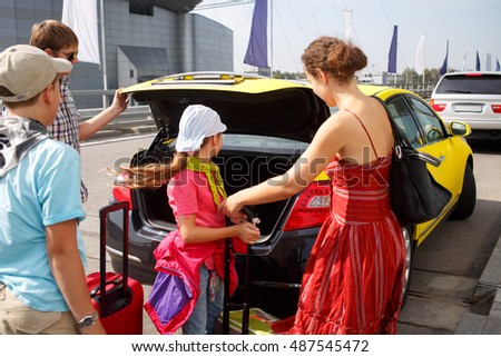 mother with two children puts luggage in the trunk of taxi, focus on driver