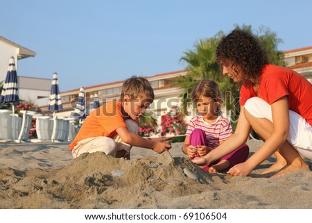 Mother with two children sits on  beach in  day-time and build  hill from sand - stock photo