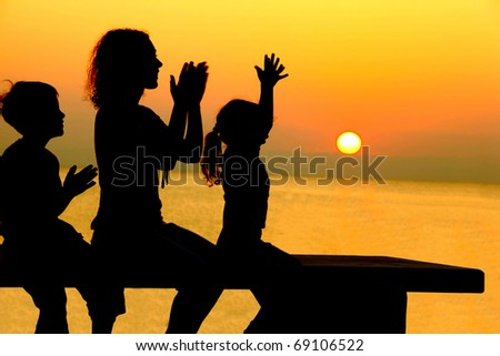 Mother with two children sits on  bench on  beach on sunset and merrily slam hands - stock photo