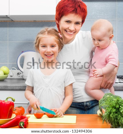 Mother with two daughters in the kitchen with vegetables - stock photo