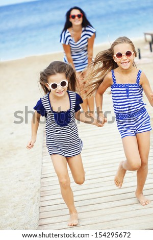 Mother with two daughters resting at the beach in summer - stock photo