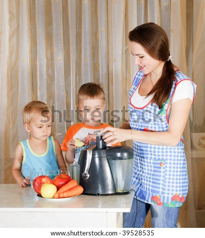 Mother with two kids doing juice from juicing machine at kitchen
