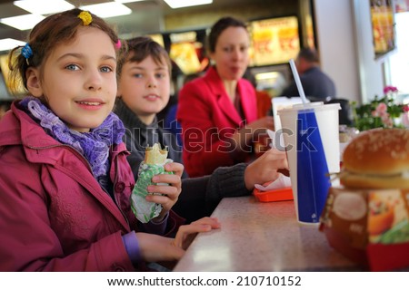 Mother with two kids have a snack in a fast food restaurant - stock photo