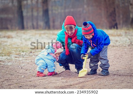 mother with two kids playing in winter park - stock photo