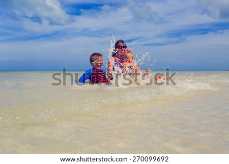 mother with two kids splashing water at the sea beach