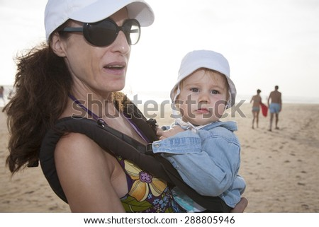 mother with white cap black sunglasses blue jeans shorts carrying her one year baby with hat in front rucksack walking at a beach - stock photo