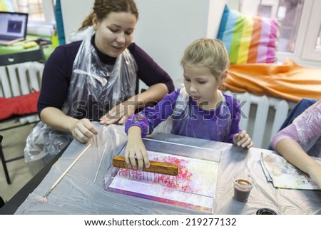 Mother with young daughter learning to make ebru drawing at workshop - stock photo