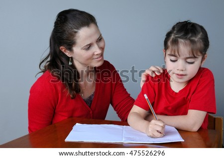 Mother (woman age 30-35) helping her daughter (girl age 6 -7) with her school project at home. Family lifestyle and education concept