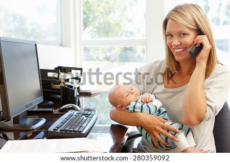 Mother working in home office with baby - stock photo