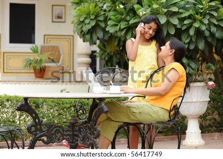 Mother working on computer with daughter in house garden - stock photo
