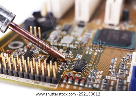 Motherboard repairing on white background - stock photo