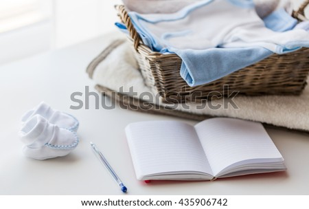 motherhood, care, parenthood and object concept - close up of pile of baby clothes with towel for newborn boy in basket and blank notebook or diary on table - stock photo