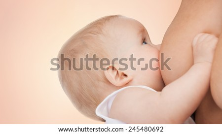 motherhood, children, people and care concept - close up of mother breast feeding adorable baby over beige background - stock photo