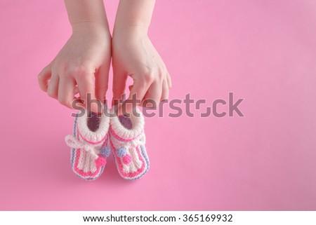 Motherhood concept. Female hold tiny newborn booties - stock photo