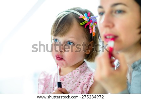 Motherhood. Little girl imitating her mother who is applying lipstick in front of a mirror. - stock photo
