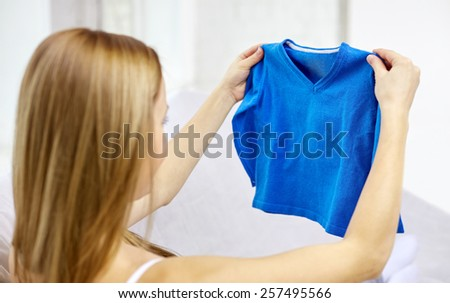 motherhood, people and kids clothing concept - happy woman holding and looking at little boys blue pullover at home - stock photo