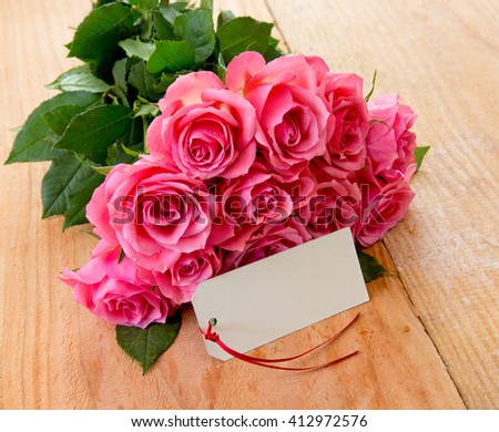 Mothers day background with pink roses over wooden table.