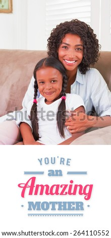 mothers day greeting against pretty mother sitting on the couch with her daughter smiling at camera - stock photo