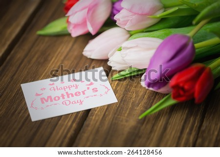 mothers day greeting against tulips on desk